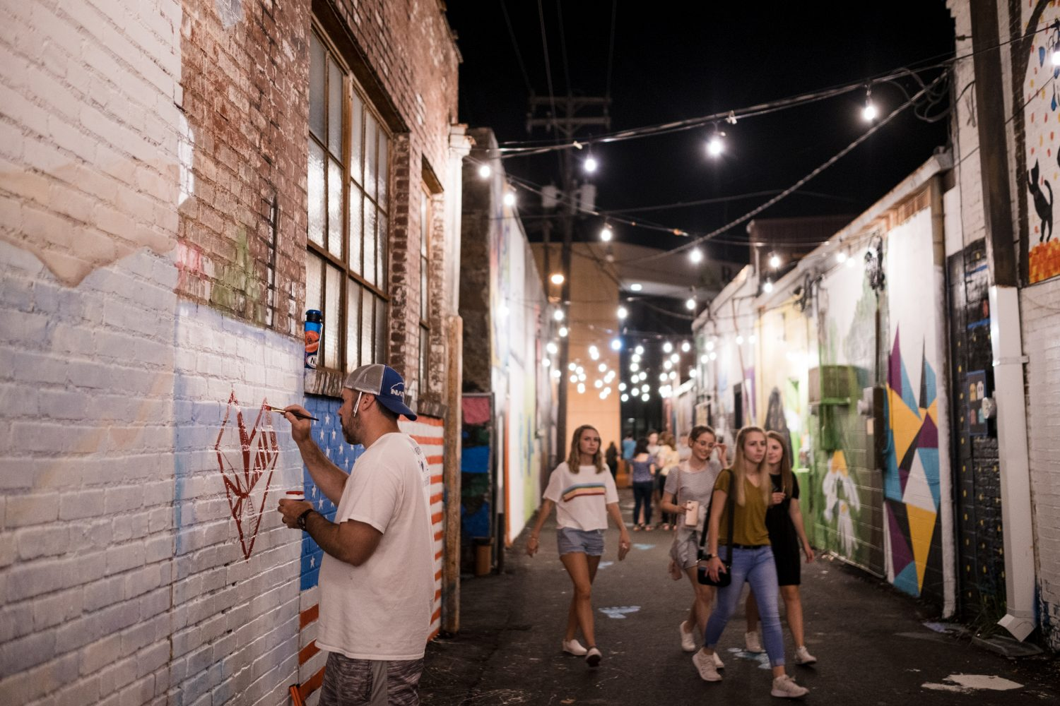 Local artists work on Art Alley murals live at downtown events like First Friday Art Night and Beats and Eats.
