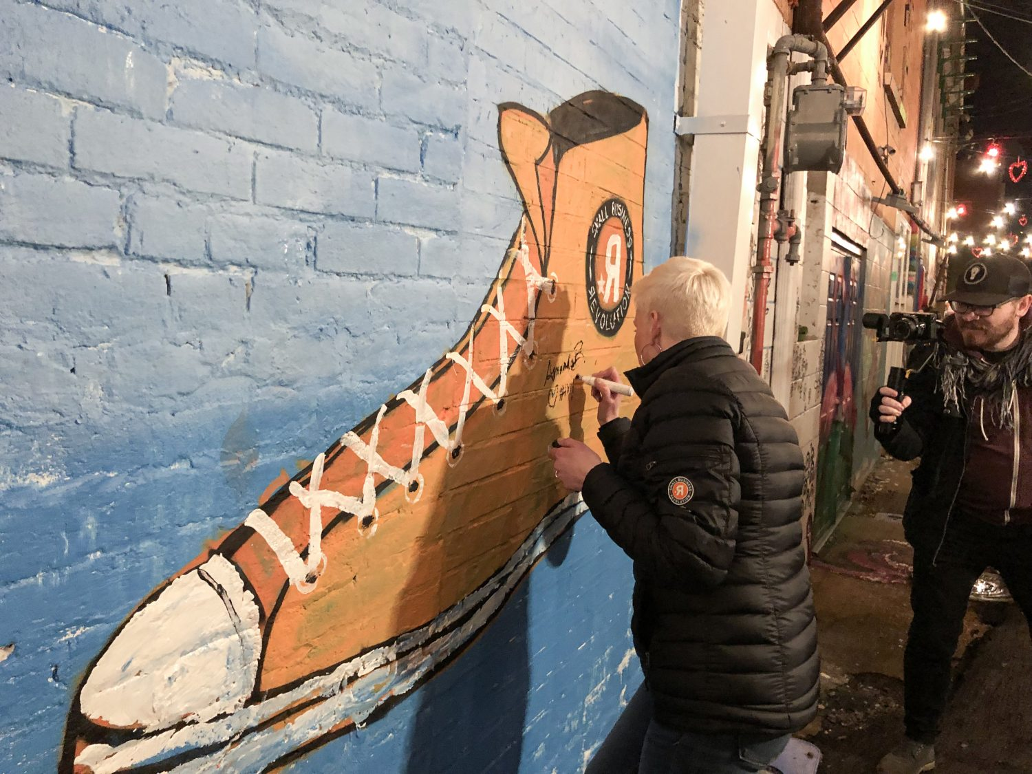 """SBR's Amanda Brinkman made sure to sign the """"Shoe"""" mural in Art Alley while she was in town."""